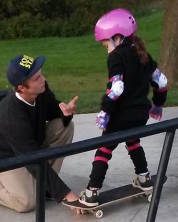 teen helps young girl learn to skateboard