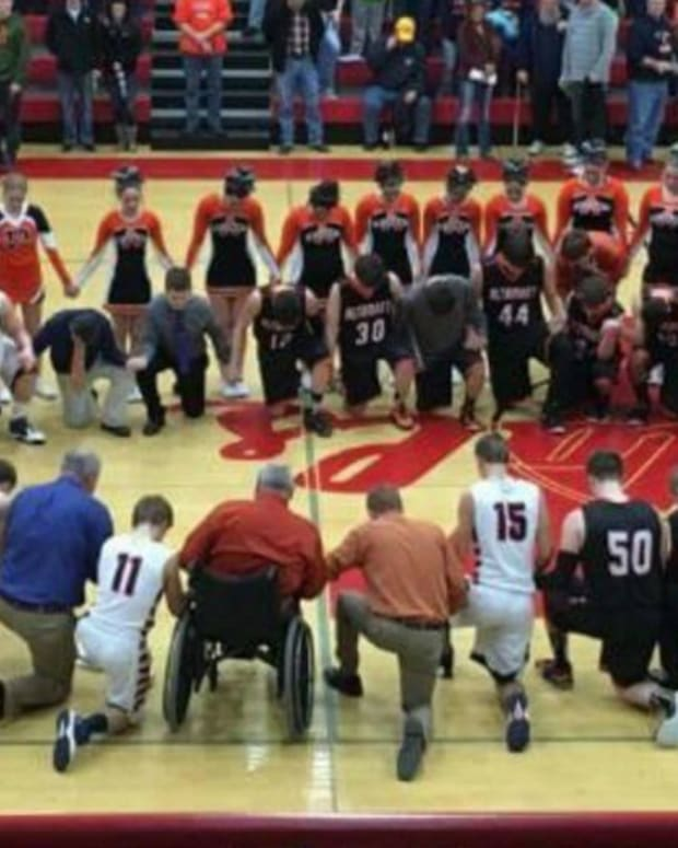 a high school basketball team praying at a game