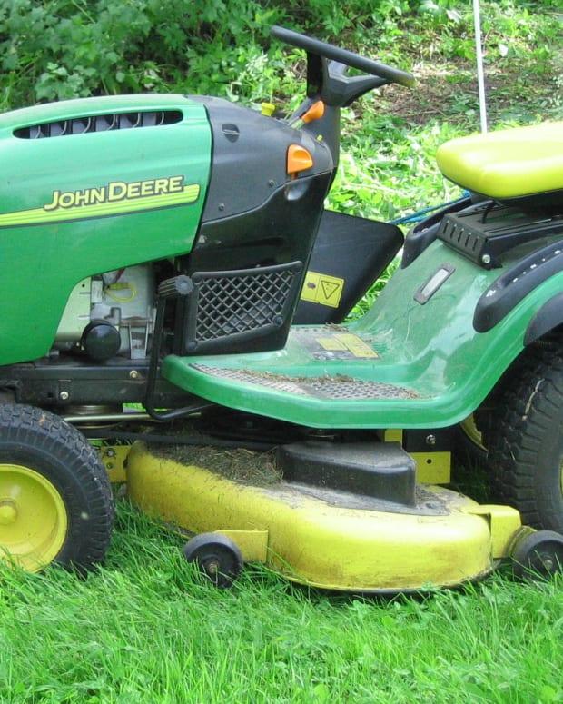 John Deere Lawn Mower On Uncut Grass.
