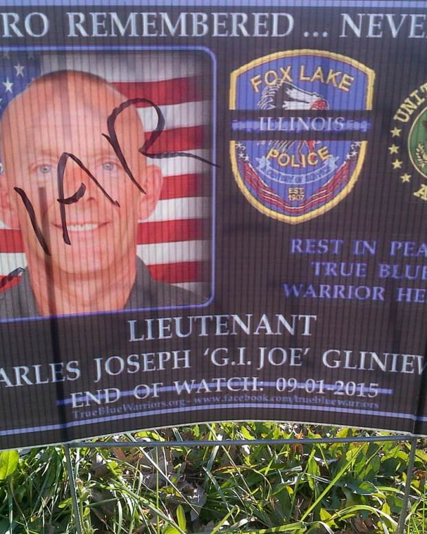 A poster honoring Lt. Joseph Gliniewicz with 'LIAR' written over his photo