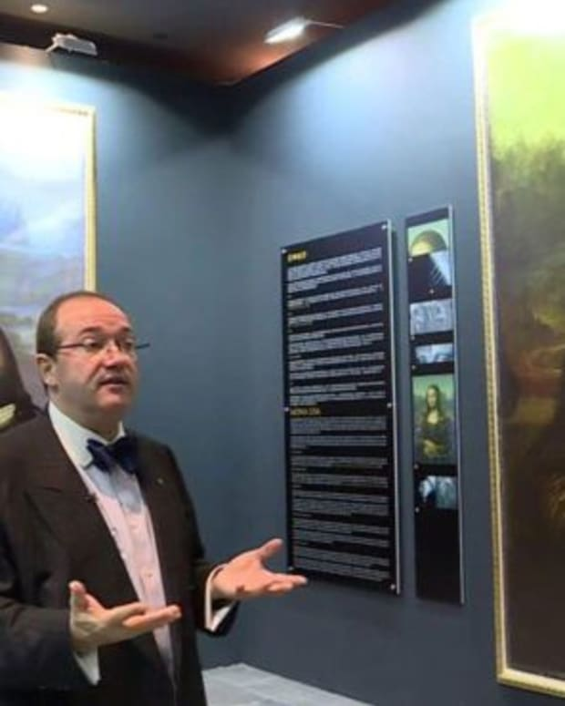 French scientist Pascal Cotte stands next to a digital reconstruction of a portrait that may be underneath the Mona Lisa