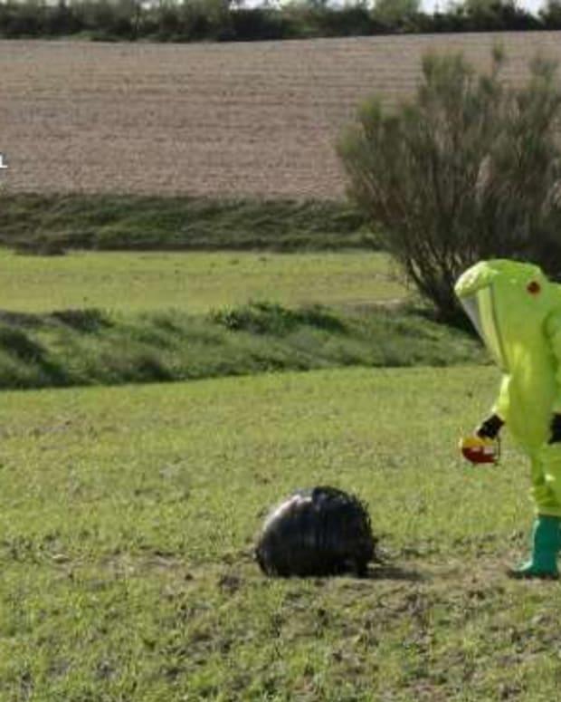 Civil Guard members examine space debris