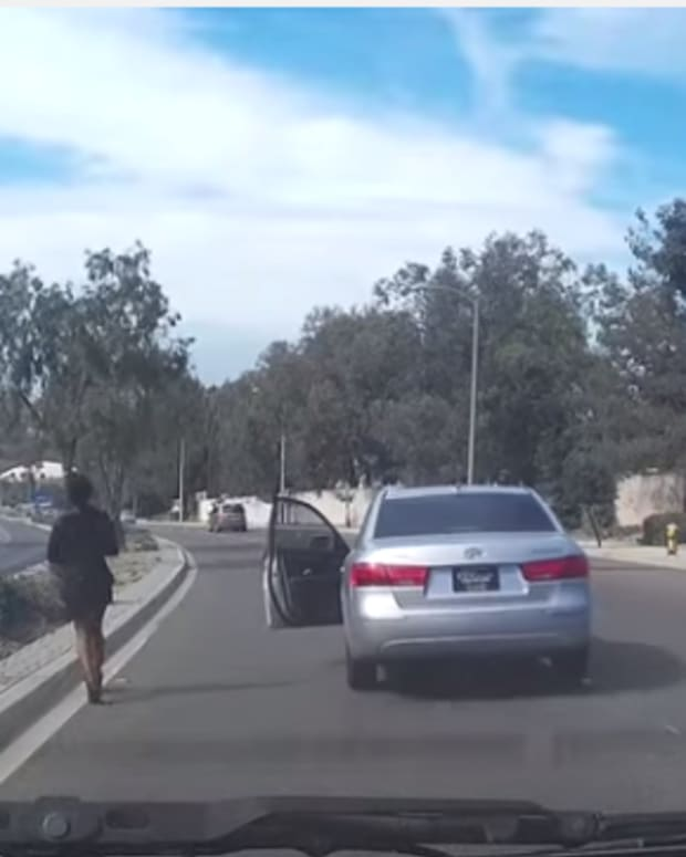 Screenshot of dash cam footage, woman getting out of car