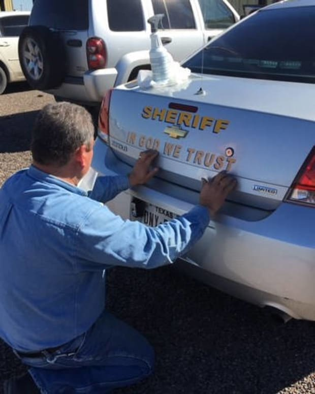 an Ector County Sheriff adds the 'In God We Trust' decal to a patrol car