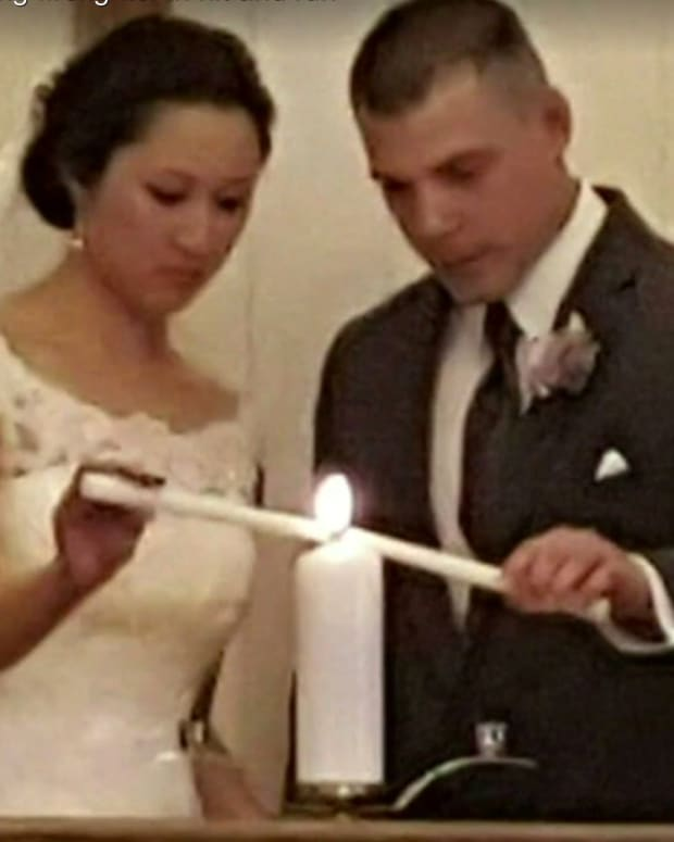 Dennis Rodeman and his wife lighting a candle at their wedding