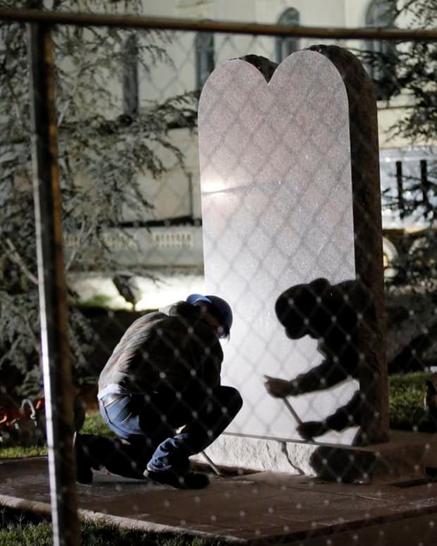 A worker pries at the base during the removal of the Ten Commandments monument from the state Capitol in Oklahoma City