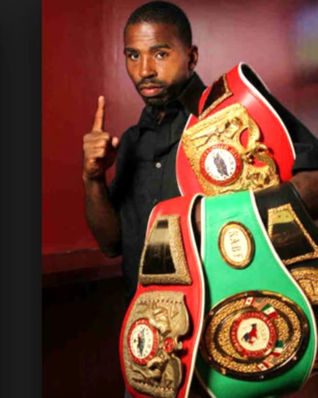 Yusaf Mack holding his title belts