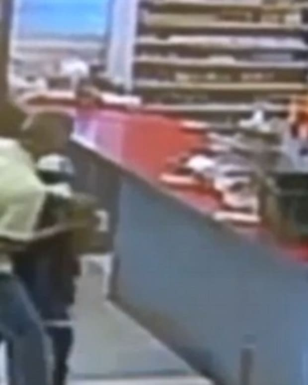 Surveillance footage of a boy robbing a store at gunpoint