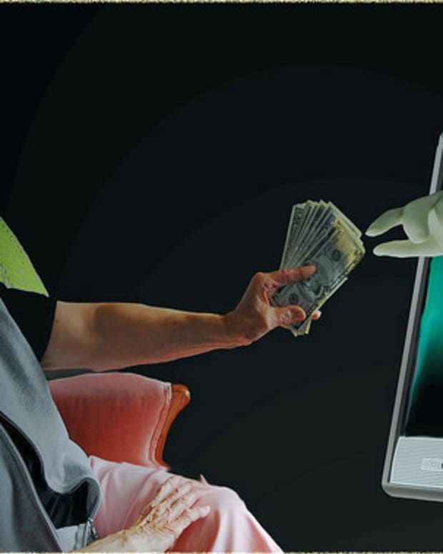 elderly woman handing money to computer (stock photo)