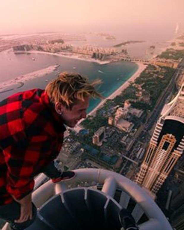 Men doing stunts on top of skyscraper