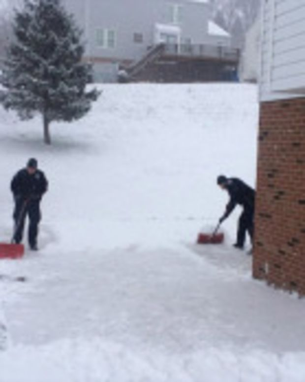 Police officers shoveling snow