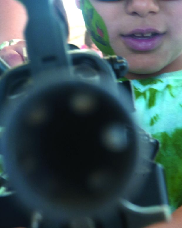 person pointing a gun at the camera