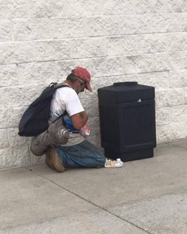 man looking for food in trash can