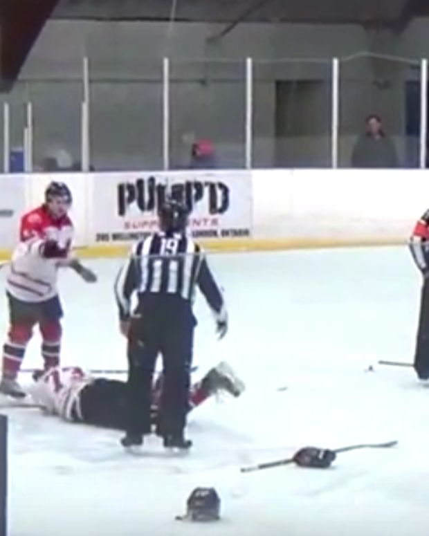 hockey player on the ground after referee punches him