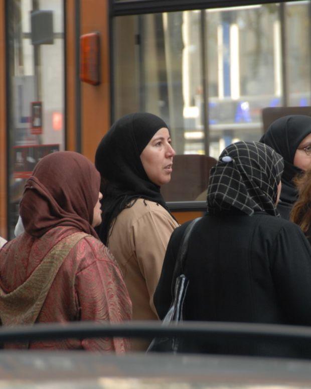 Women wearing headscarves wait for a bus