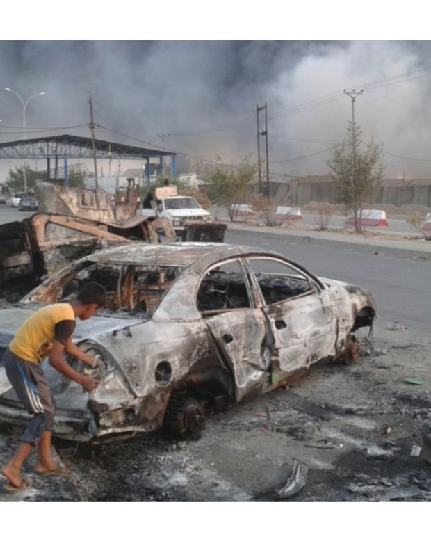 Two young boys next to a burned vehicle in Mosul