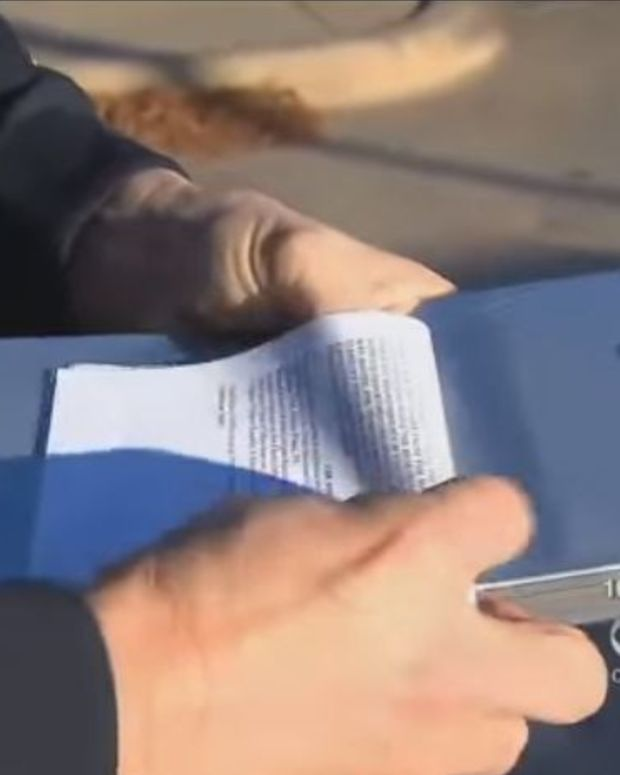 Officer Hands Man Traffic Ticket, Man Immediately Notices Something Rolled Up Inside Of It (Video) Promo Image
