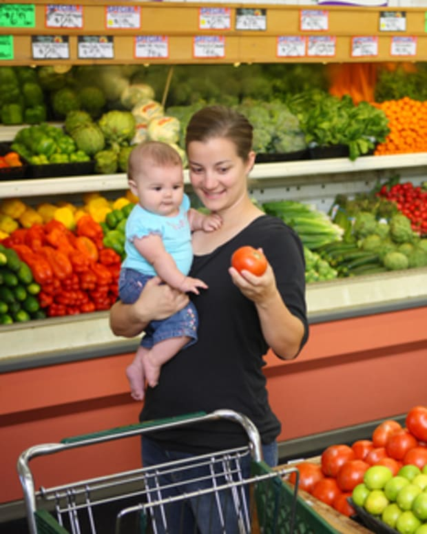 Woman grocery shopping with baby