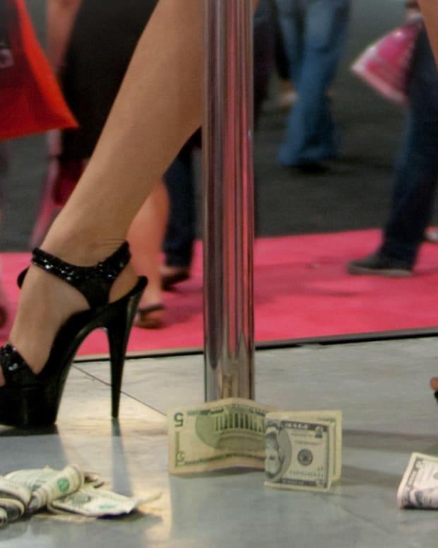 money at the feet of woman wearing high heels near stripper pole